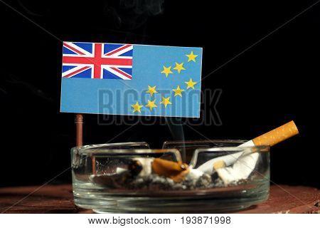 Tuvalu Flag With Burning Cigarette In Ashtray Isolated On Black Background