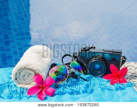 Red frangipani (plumeria) flowers sunglasses beach hat blue towel retro film camera and sunscreen at the side of swimming pool. Vacation beach summer travel concept