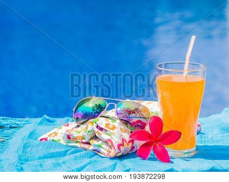 Red frangipani (plumeria) flowers sungrasses shampoo lotion hat rolled up towels and Orange juice with a piece of lemon at the side of swimming pool. Vacation beach summer travel concept