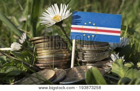 Cape Verde Flag With Stack Of Money Coins With Grass And Flowers