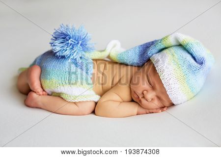 lovely newborn baby in knitted hat and panties sleeps curled up, top view