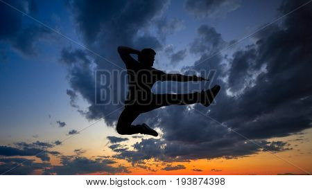 Silhouette of a man against a background of clouds and golden sunset. He is jumping on the roof. Parkour in the evening.