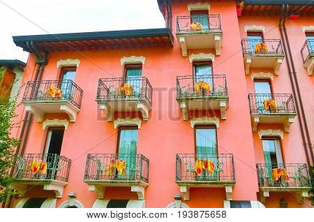 Beautiful red fasade with balconys of house at old town at Sirmione town, Italy.