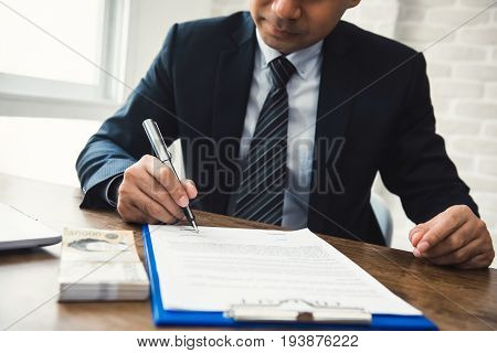 Businessman signing contract with money South Korean Won banknotes on the table