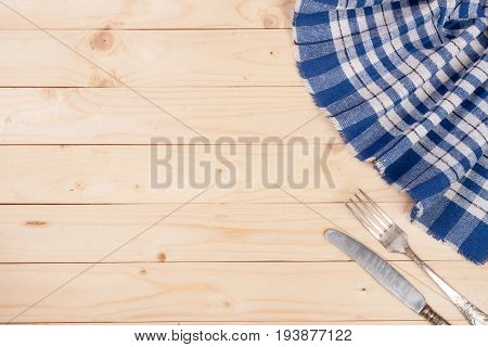 blue checkered tablecloth with knife and fork on a light wooden table with copy space for your text. Top view.