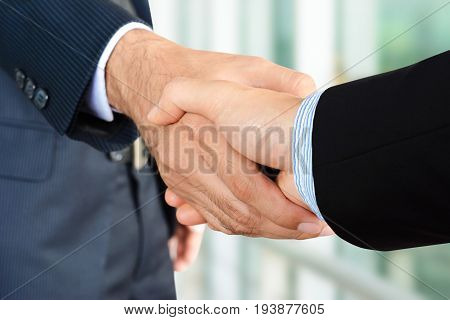 Close up of businessman hands making handshake - greeting dealing merger and acquisition concepts