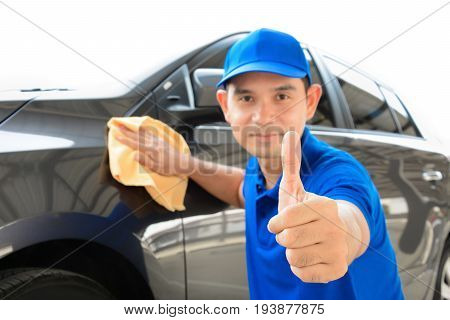 A man giving thumbs up while cleaning car auto detailing (or valeting) concept