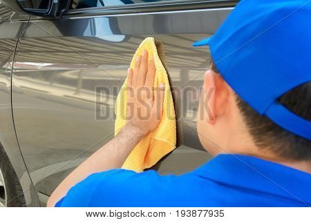 A man polishing car with microfiber cloth car detailing (or valeting) concept