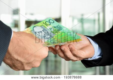 Hands of businessmen passing money Australia dollar bills