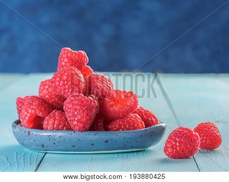 Fresh raspberries on blue wooden background. Raspberry in blue trandy plate. Summer and healthy food concept. Copy space.