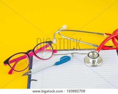 Stethoscope with clipboard pen and glasses on yellow background for Doctor working in hospital writing a prescription Healthcare and medical concept