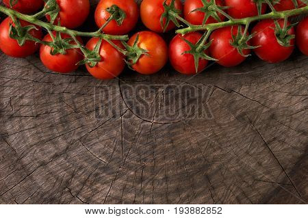 Close-up of Tomatoes. View from above of a Cherry tomatoes. Fresh grape tomatoes on a branch on wooden background. Top view with copy space. Healthy eating and detox concept.