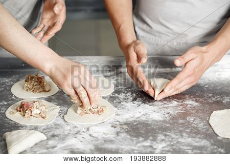 Selective focus. billet bun of dough with filling inside. Prepared for baking in baking production. manufacturing of food products. Baker lays out the filling on the workpiece. hands closeup. the concept for the site bakery