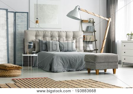 Comfortable bed with quilted headboard and grey pillows