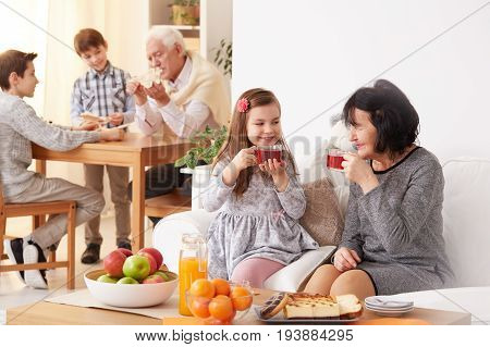 Lovely grandmother and beautiful granddaughter drinking delicious warm tea