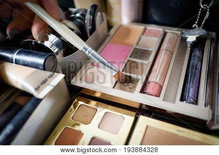 Make-up artist using brush to apply pressed eye shadow palette.
