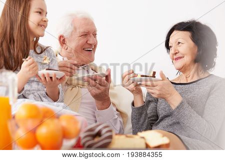 Smiling grandparents and lovely granddaughter eating delicious homemade cake