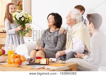 Lovely granddaughter giving beautiful bouquet of flowers to happy grandparents