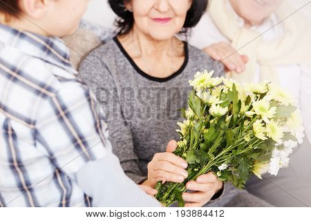 Young boy giving bouquet of beautiful flowers to his elegant grandparents