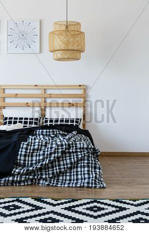 Wooden bed with black and white bedding in spacious bedroom