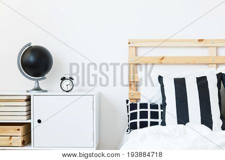 White nightstand with books and black globe near the wooden bed