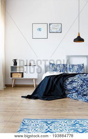 Blue accessories in modern designed bedroom with wooden floor