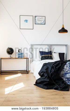 Elegant design of bedroom with wooden floor and white bed