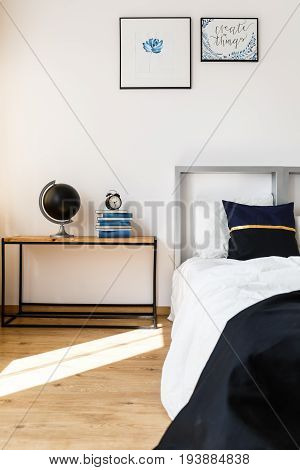 Wooden nightstand in white cozy bedroom with black accessories