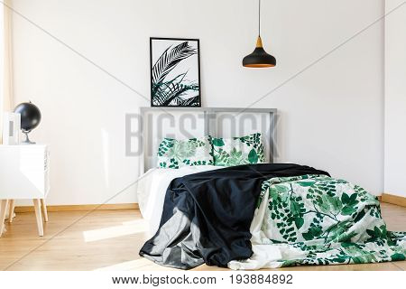 Cozy bed with floral green and white bedding and black blanket