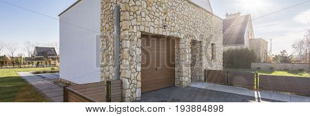 Big house with stone wall and garage in the backyard