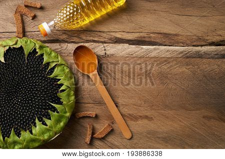 Close-up of a yellow sunflowers bottle with oil and sunflower oil in the wooden spoon on old rustic table .