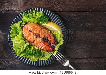 An overhead photo of a grilled salmon steak, with fresh green salad, broccoli sprouts, a slice of lemon, and pink peppercorns, with a fork, on a dark rustic background with a place for text