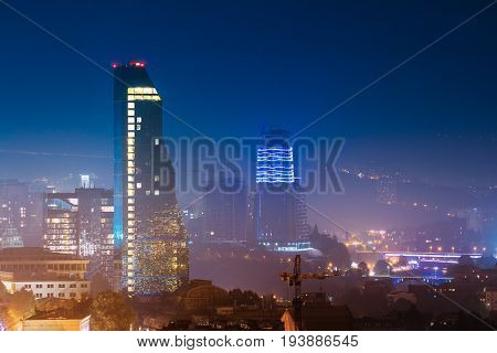 Tbilisi, Georgia - October 21, 2016: Construction Development Of Modern Architecture On Background Of Urban Night Cityscape. Evening Night Scenic Aerial View Of City Center.