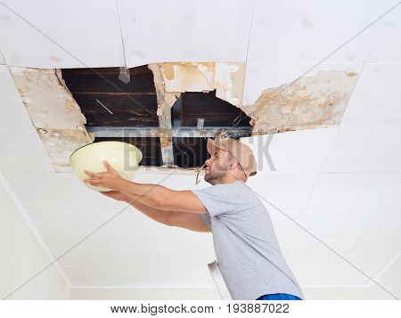 Man Collecting Water In Basin From Ceiling. Ceiling Panels Damaged Huge Hole In Roof From Rainwater