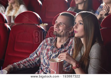 Lovely young couple watching a movie together during their date at the cinema copyspace people lifestyle leisure entertaining films premiere concept.