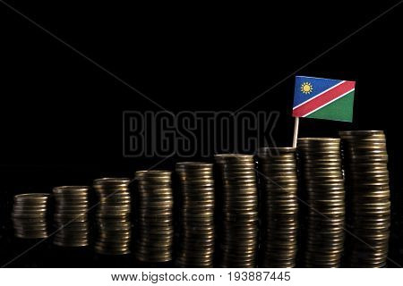 Namibian Flag With Lot Of Coins Isolated On Black Background