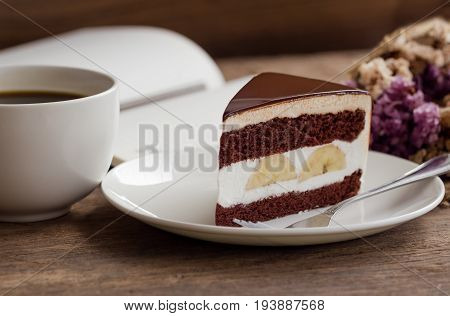 Banana chocolate cake on white plate served with black coffee. Chocolate cake layered with whipped cream and banana look so delicious. Enjoy eating at cafe restaurant with chocolate cake and coffee. Banana chocolate cake ready to served.