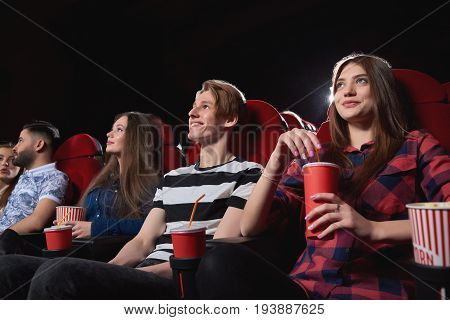 Low angle shot of happy young people smiling enjoying watching a movie at the cinema comedy premiere film spectators audience emotions positivity entertain concept.