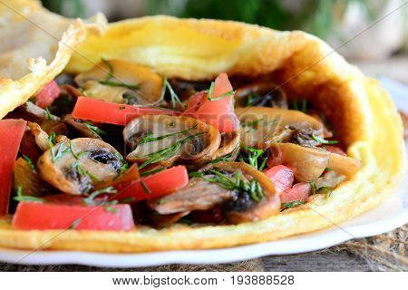 Vegetarian omelette recipe. Homemade omelette stuffed with chopped fresh tomatoes and fried mushrooms. Closeup
