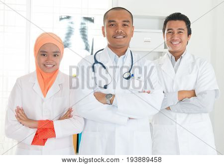 Medical team crossed arms standing inside hospital. Southeast Asian Muslim doctors and nurses.