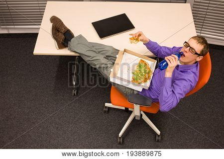fast meal in office - man drinking water, heaving break for pizza