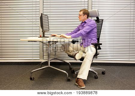 sitting position at workstation. man on chair working with computer stretching leg