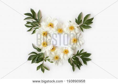 Mother`s Day concept. Blank paper with heart-shaped floral frame made of white peony flowers and big green leaves. Top view flat lay postcard.