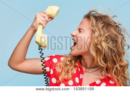 Blonde curly haired woman wearing red dress with white dots yelling at phone receiver standing against blue background.