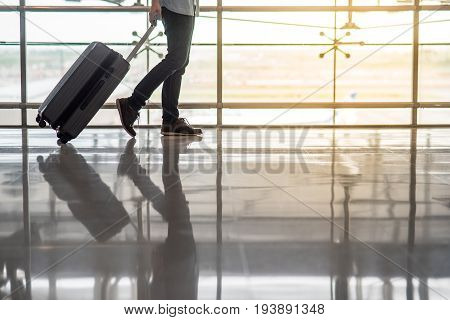 Reflection of half male body walking in the airport terminal with suitcase luggage travel background with copy space