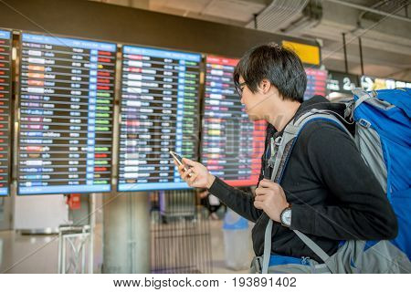 Young asian man with backpack bag checking for his flight from the flight information board and holding smartphone at airport terminal