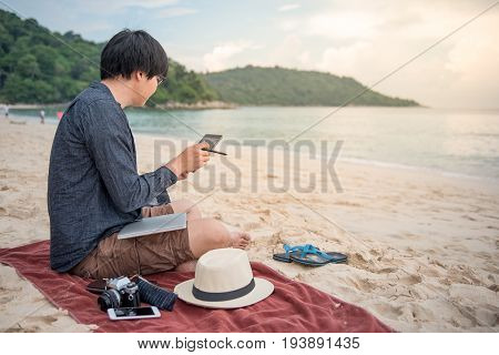 Young Asian man using tablet on tropical beach digital nomad or freelance lifestyle concepts
