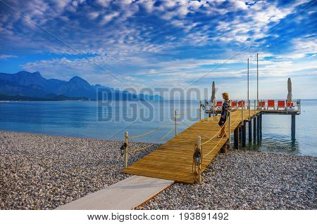 Woman on the beach of the city of Kemer looks at the mountains.