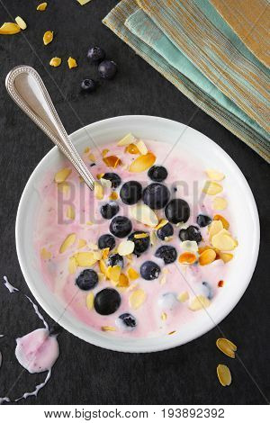 Fresh yogurt with blueberries and almond slivers on dark backdrop, with silver spoon and turquoise napkin