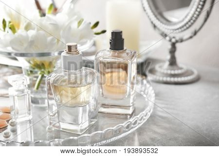 Glass tray with perfume bottles on grey table